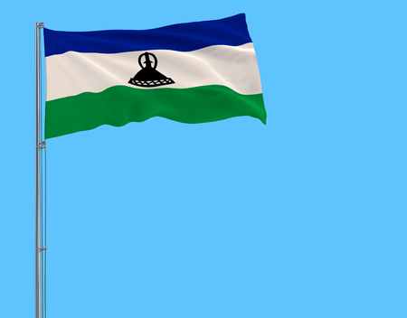 Isolate flag of Kingdom of Lesotho on a flagpole fluttering in the wind on a blue background
