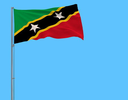 Isolate flag of Saint Kitts and Nevis on a flagpole fluttering in the wind on a blue background, 3d rendering Stock Photo