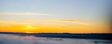 Predawn morning fog and orange-blue sky with clouds.