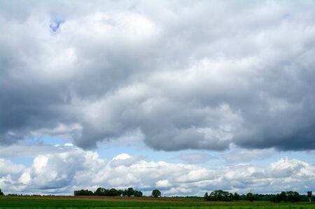Landscape with clouds over fields and a forest in the distance.
