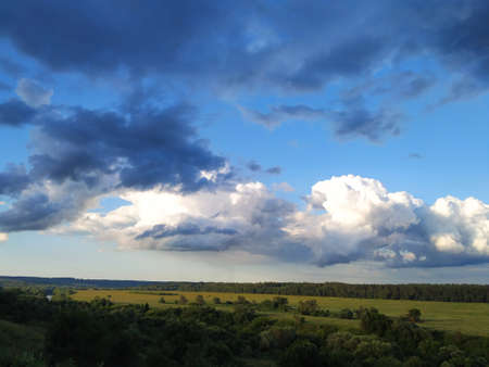 Dark blue and white clouds over the fields and the river, smart
