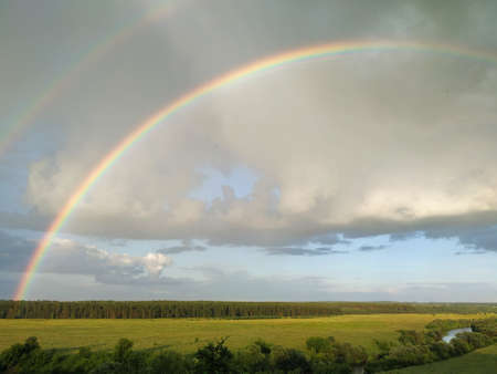 Rainbow and clouds over fields and river, smart. Archivio Fotografico