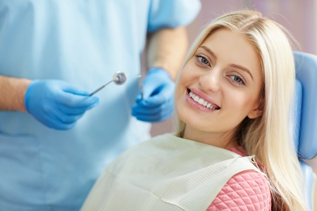 dental nurse: treatment of the patient girl in the dental clinic