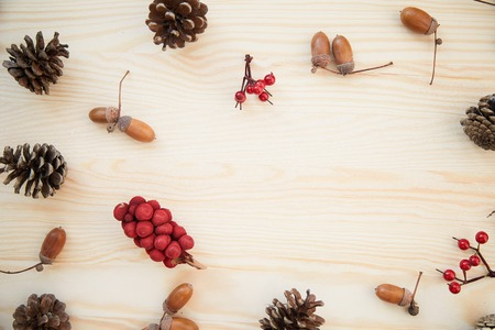 Christmas frame: cones, cinnamon, berries, acorn on the wood table