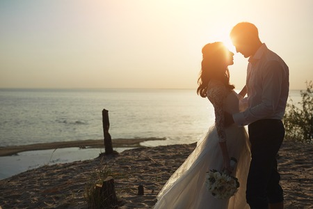 recien casados: Apenas pares casados ??que se ejecutan en una playa de arena