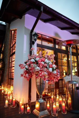 Beautiful candles with flowers near house, evening Stock fotó