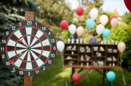 Dartboard with ballons on background, game