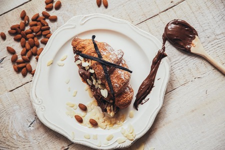 Tasty croissant with chocolate on plate on white wooden background Stock fotó