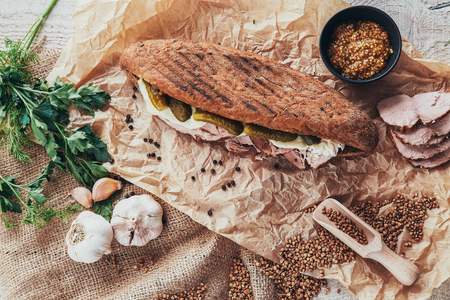 rustic panini on wooden board with garlic, cucumber and ham
