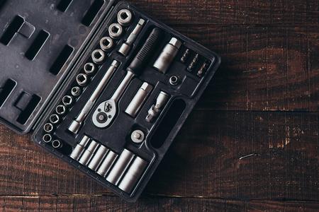 kit of metallic tools on wooden background