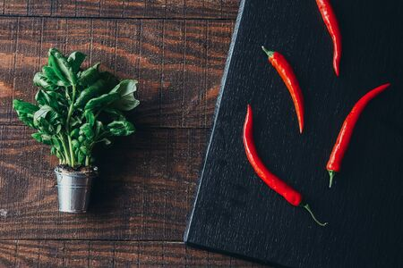 chili peppers and plant on a wooden background