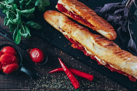long baguette sandwich with lettuce, vegetables, salami, chili and cheese on black background