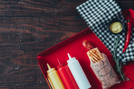 Hot dog with mustard, ketchup and mayonnaise on wooden background. Top view