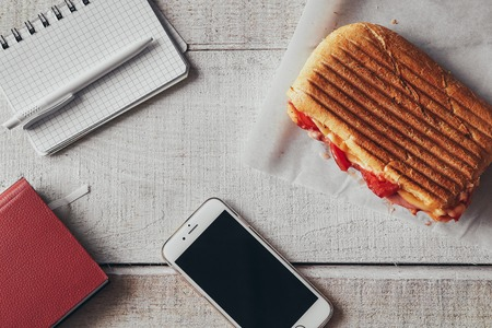 Panini with cellphone, pen and notepad on office wooden table