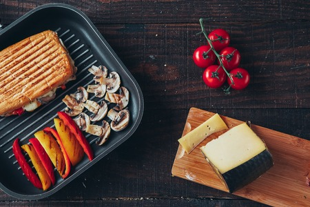A delicious griled panini sandwich with mushrooms, cheese, pepper and tomato