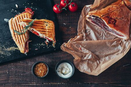 cooking tasty panini with ham covered with cheese, tomatoes and flavoring Stock fotó