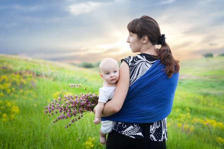 draagdoek: moeder en baby jongen in draagdoek op de groene weide bloemen te verzamelen bij zonsondergang in de zomer Stockfoto