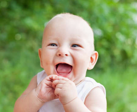 Portrait of smiling happy baby boy on natural background in summer  Фото со стока