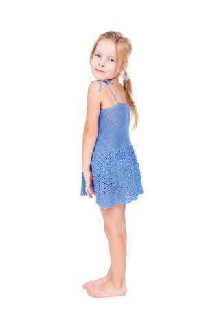 is embarrassed: shy pretty little girl in blue dress