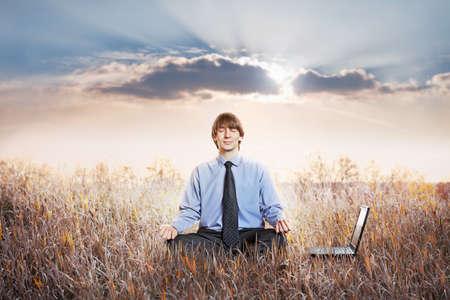 meditating: Businessman meditating in lotus pose. Business yoga