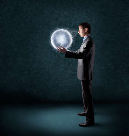 businessman holding glowing planet earth