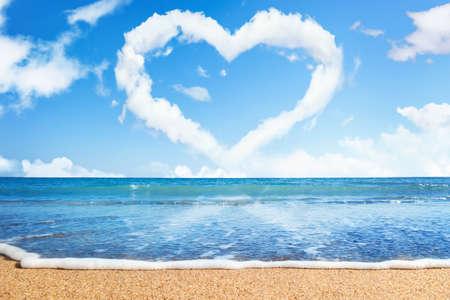 liefde: strand en zee. Hart van wolken op hemel. Symbool van de liefde