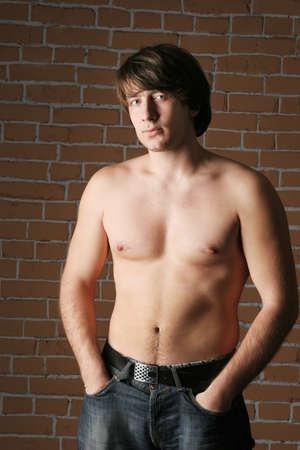 niño sin camisa: macho cerca de una pared de ladrillo