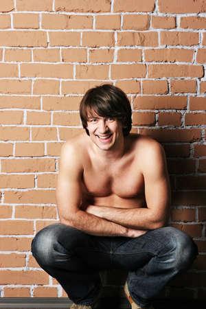 niño sin camisa: sonriendo macho cerca de una pared de ladrillo