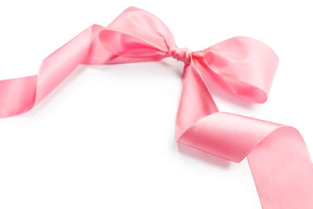 shiny pink satin holiday ribbon and bow isolated on white background with copy space