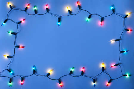 Christmas lights frame on dark blue background with copy space.Decorative garland  photo
