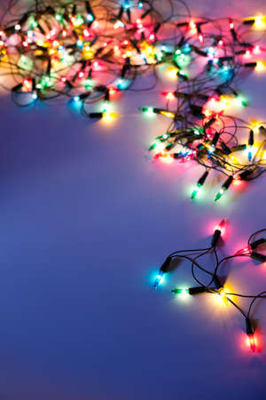 Christmas lights on dark blue background with copy space. Decorative garland photo