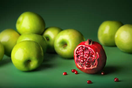 stranger: Still-life of pomegranate with green apples on darkly green background, different concepts - red pomegranate before green apples Stock Photo