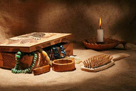 textura: Still-life con cofanetto in legno, ornamenti, spazzola per capelli e candela su sfondo strutturale