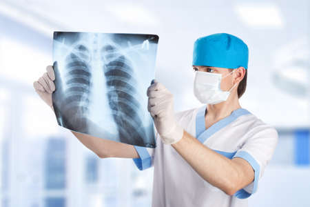 medical doctor looking at x-ray picture of lungs in hospital photo