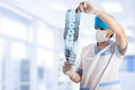 médico mirando la imagen de rayos x de columna vertebral en el hospital con espacio de copia  Foto de archivo