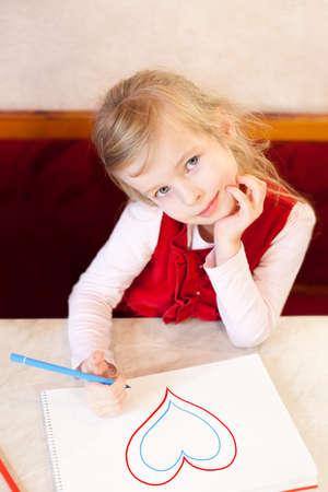 soft tip pen: smiling little girl draws heart in an album. Valentine Stock Photo