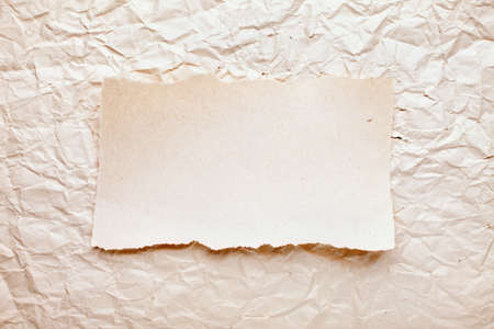 ripped piece of paper on old crushed paper background. vintage retro card Stock Photo - 10332310