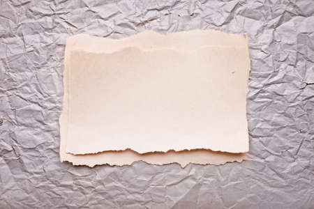 ripped piece of paper on old crushed paper background. vintage retro card  photo