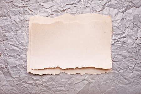 zerrissenen Stück Papier auf alten zerdrückten Papier Hintergrund. Retro-Karte