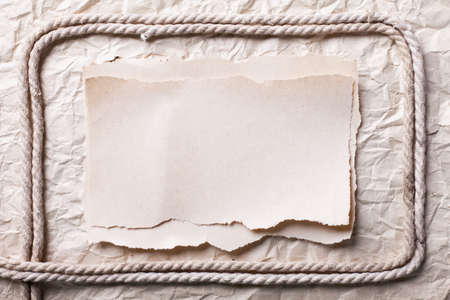 ripped piece of paper and rope on old crushed paper background. vintage retro card Stock Photo - 10332301