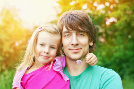 father and daughter.Young man and beautiful little girl outdoors in park  in summer photo