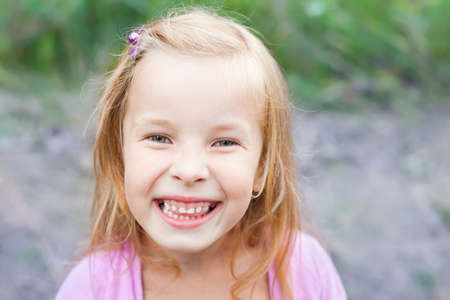giggle: close up portrait of laughing blonde little girl outdoors in summer