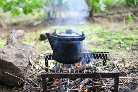 black old smoked teapot on the campfire on picnic in wood in the summer  photo