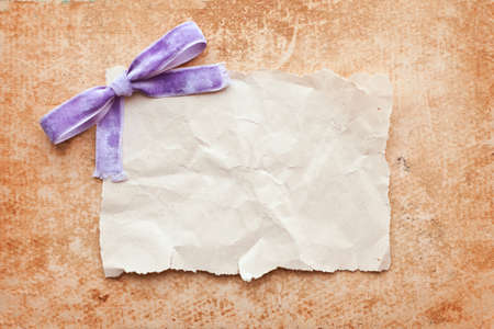 ripped piece of paper with purple bow on grunge paper background. vintage retro card Stock Photo - 10332342