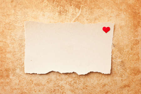 Ripped piece of paper on grunge paper background. Love letter photo