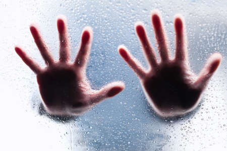 Silhouettes of two right hands behind wet glass photo