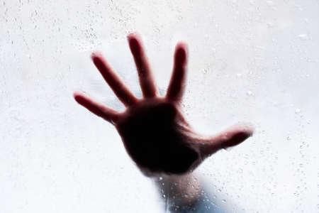 Angst: Silhouette der Hand hinter nassen Glas