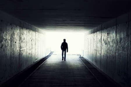 silhouet in een metro tunnel. Licht aan eind van Tunnel