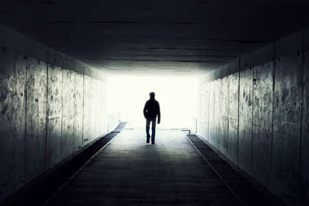 underground: silhouette in a subway tunnel. Light at End of Tunnel Stock Photo