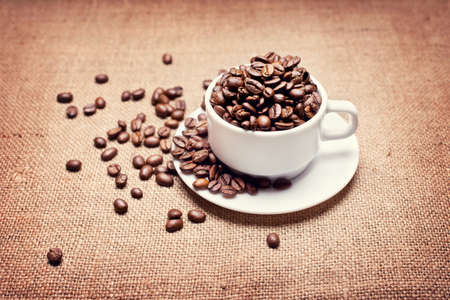 cup with coffee beans on fabric texture background  photo